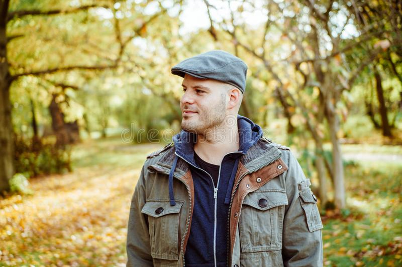 Man standing in a autumnal forest or park. Autumn, outdoors and lifestyle concept stock image