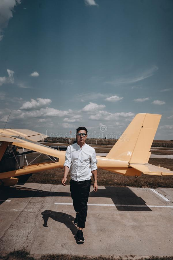 A man standing on the background of a small single engine plane. royalty free stock image