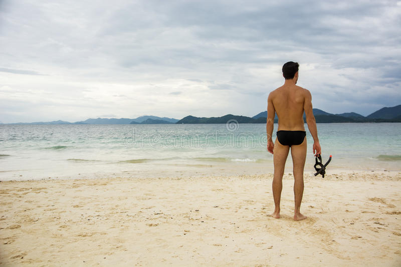 Man standing on beach. Man standing on a beach and holding scuba mask. Horizontal outdoors shot royalty free stock photo