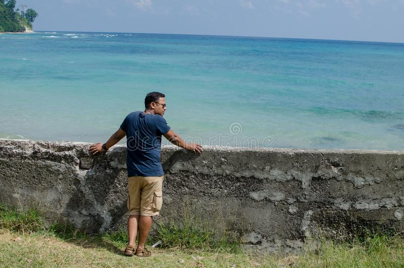 Man Standing at the beach and Looking at the sea royalty free stock image