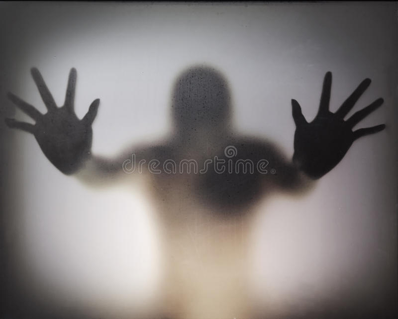 Man standing behind glass stock photos