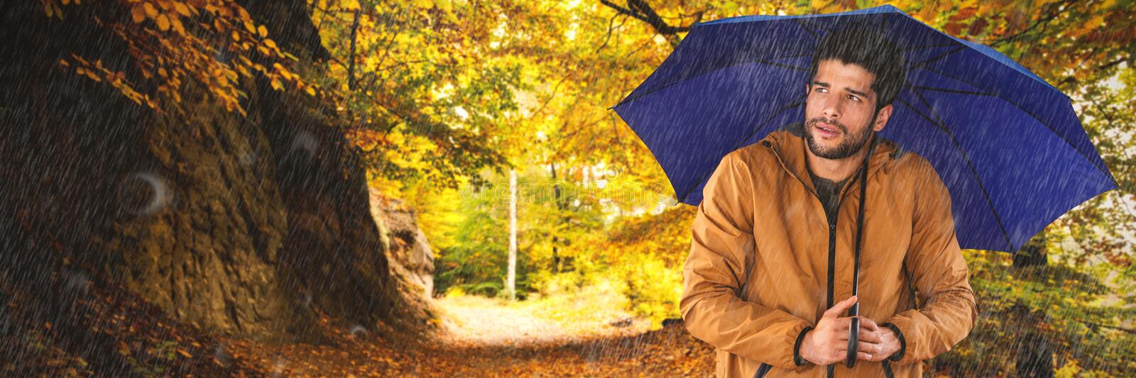 Composite image of man standing with blue umbrella royalty free stock image