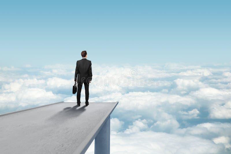 Man standing on bridge. Businessman standing on concrete bridge an looking clouds stock photography
