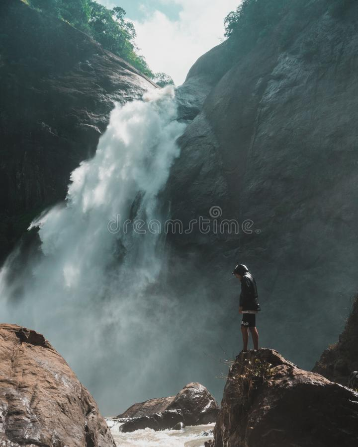 Man Standing on Brown Rock Cliff in Front of Waterfalls Photography stock image