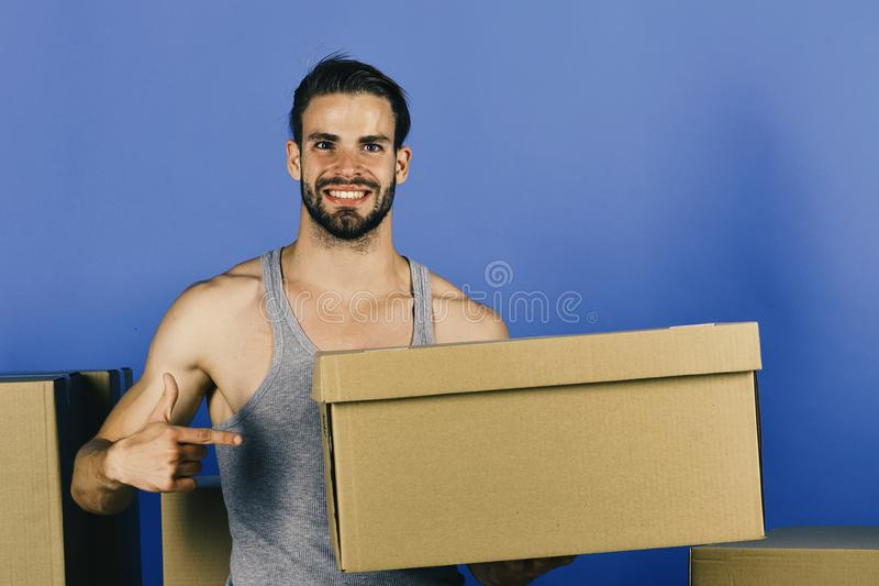 Man standing among cardboard boxes and holding one. Delivery and moving in concept: macho with beard holding box royalty free stock photo