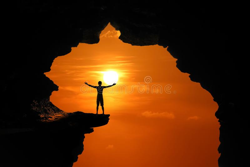 The man standing in a cave on a high cliff at red sky sunset stock images