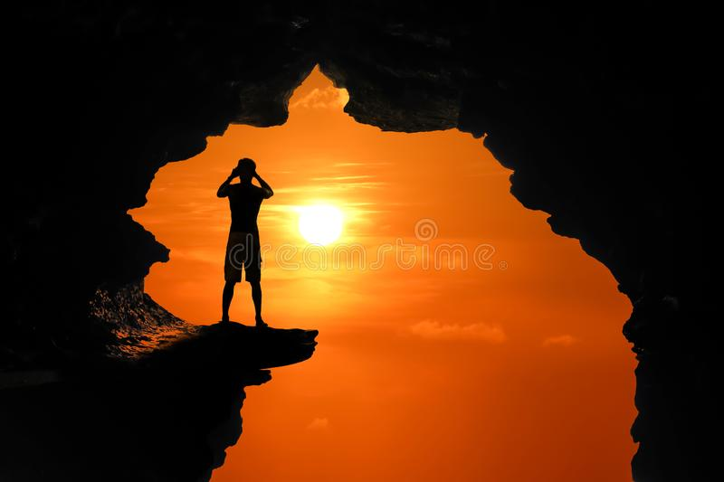 The man standing in a cave on a high cliff at red sky sunset royalty free stock images