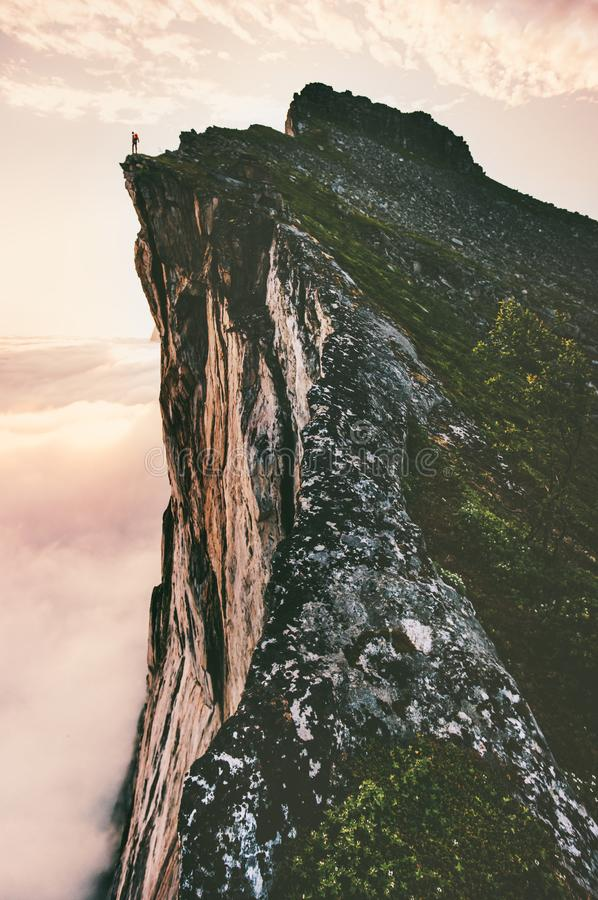 Man standing on cliff edge mountain ridge. Above sunset clouds travel adventure lifestyle summer journey vacations royalty free stock image