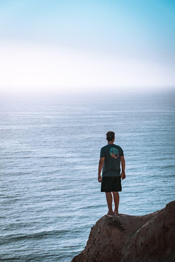 Man Standing on Cliff Near Sea royalty free stock photos