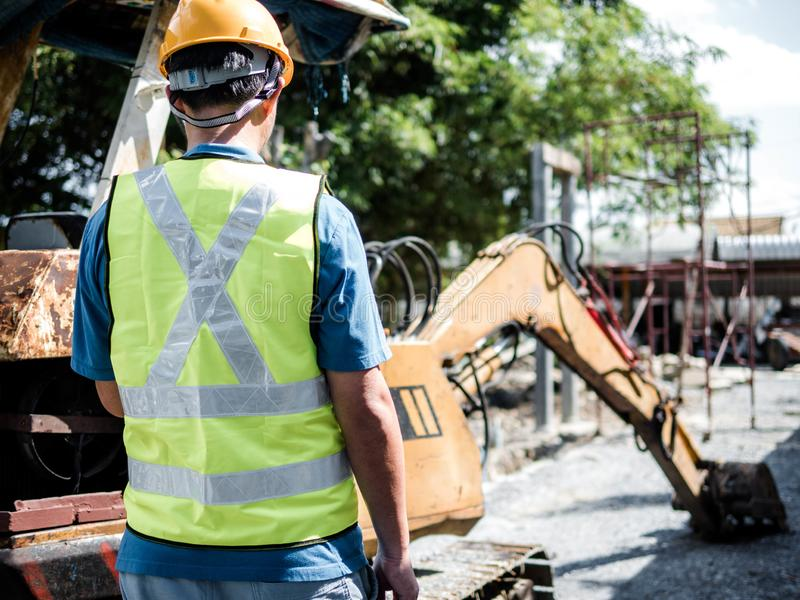 Man standing in a construction site with digger loading trucks stock photos