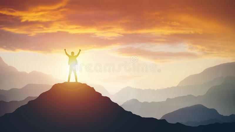 Man standing on edge of mountain feeling victorious with arms up in the air. stock photo