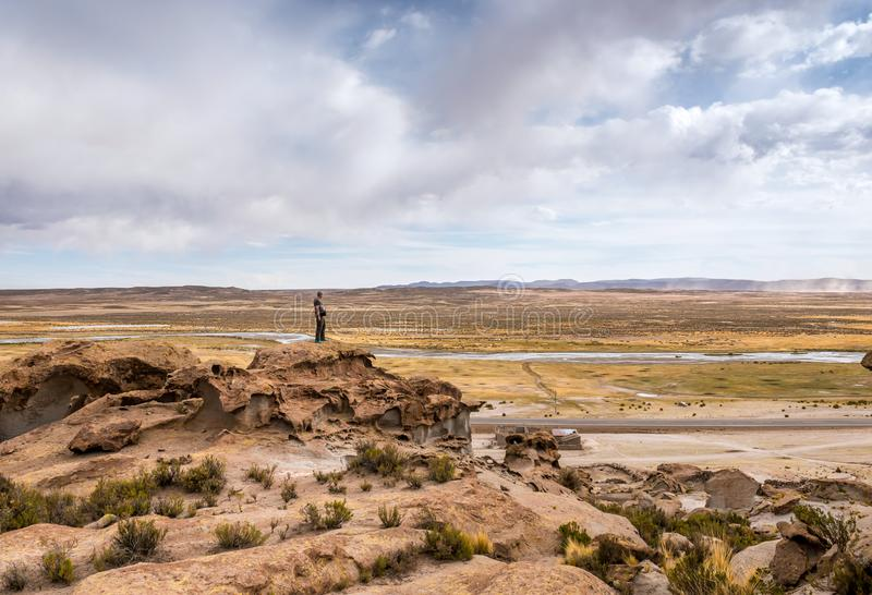 Man standing on the edge of rocky hill in Bolivia stock photography