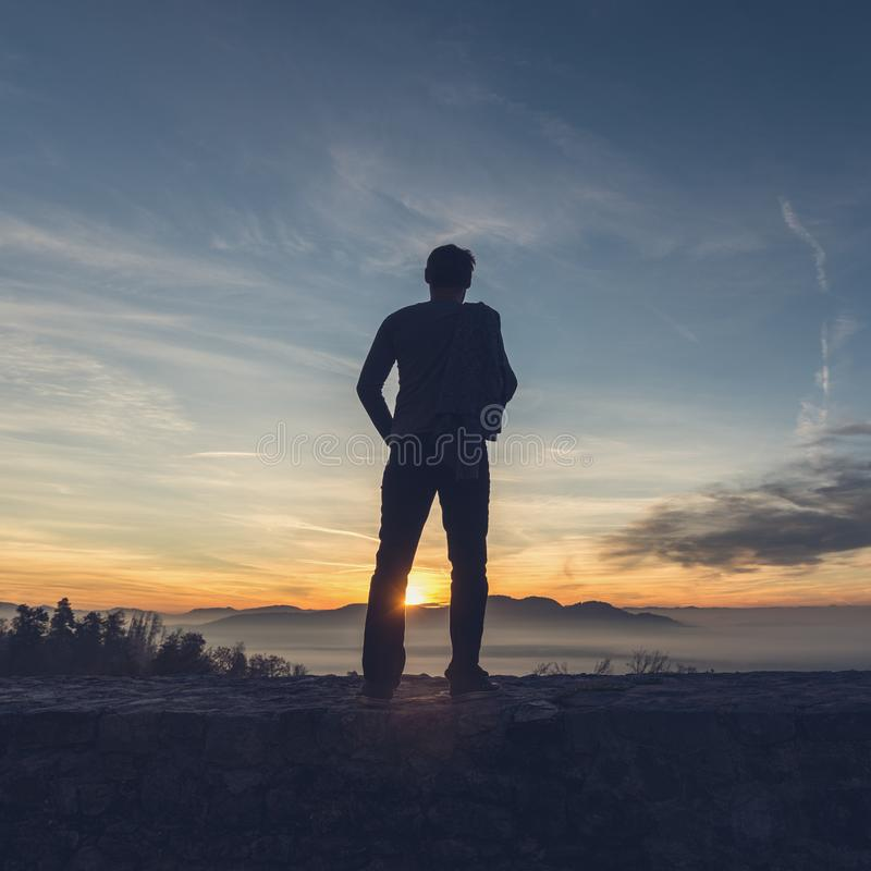 Man standing on the edge of a stone wall looking in to the distance stock photo