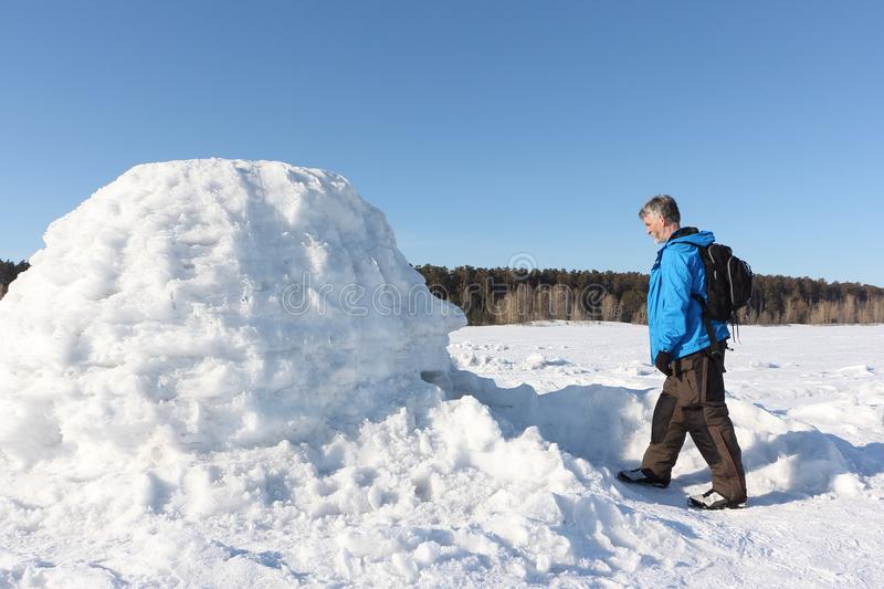 Man standing at the entrance an igloo stock photo