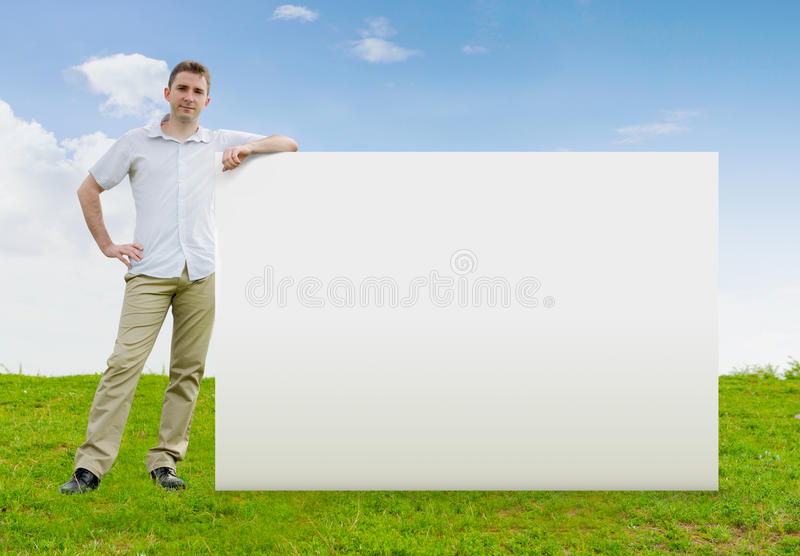 Man standing in a field with a blank sign stock images