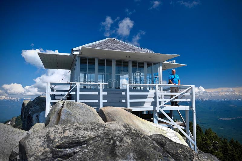 Man standing by Fire lookout hut on mountain top with expansive view. Hiking in Mount Pilchuck State Park near Seattle. Everett. WA. United States of America royalty free stock photos