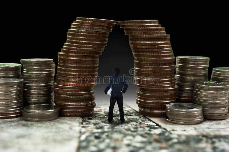 Man standing in front of giant coin pile, business concept. Image royalty free stock image