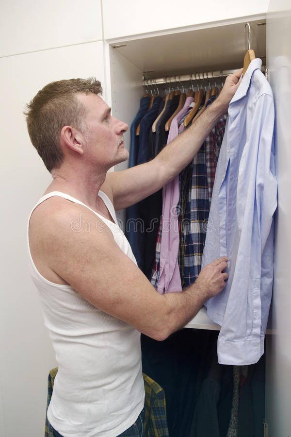 Man standing in front of his closet. And looking for a shirt royalty free stock images
