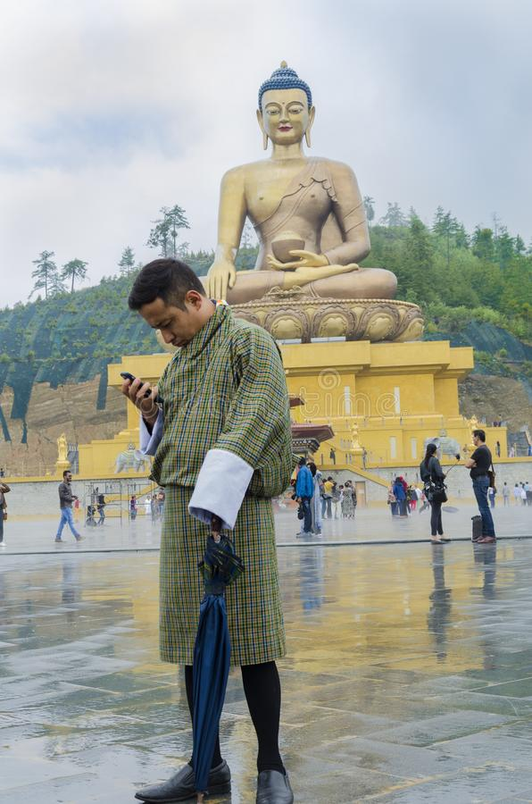 A man standing in front of large Buddha statue stock photography
