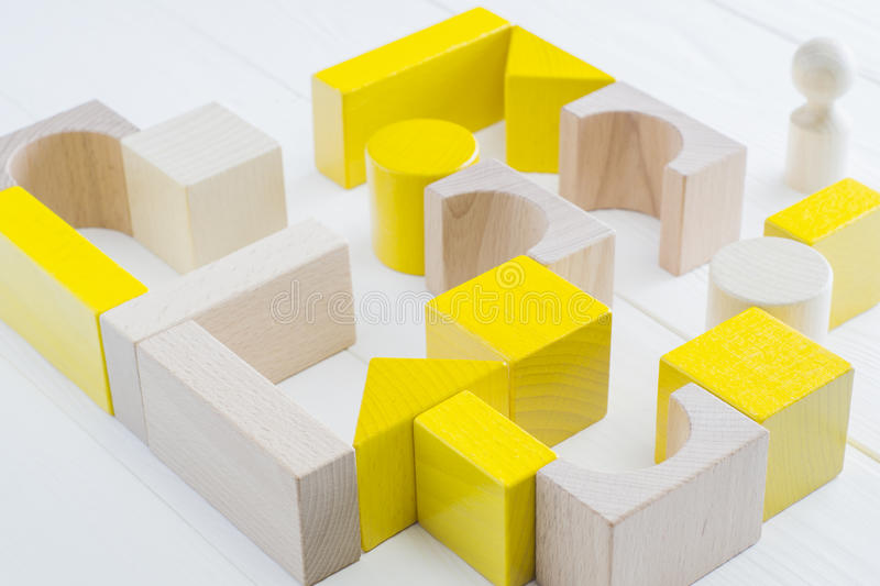 Man standing in front of the maze. The yellow-beige maze of wooden blocks of various shapes. Man standing in front of the maze. Difficult path to find exit royalty free stock photo