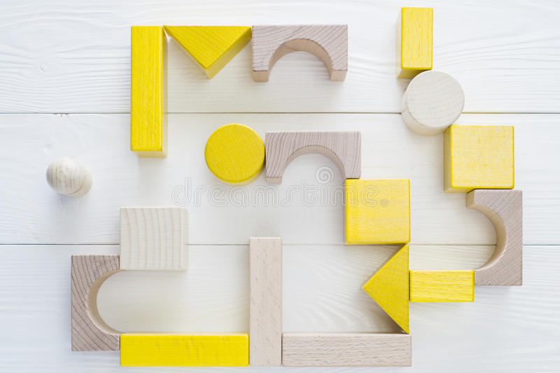 Man standing in front of the maze. The yellow-beige maze of wooden blocks of various shapes, top view. Man standing in front of the maze, flat lay. Difficult royalty free stock photos