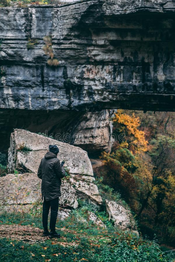 Man Standing in Front of Rock Formation royalty free stock image