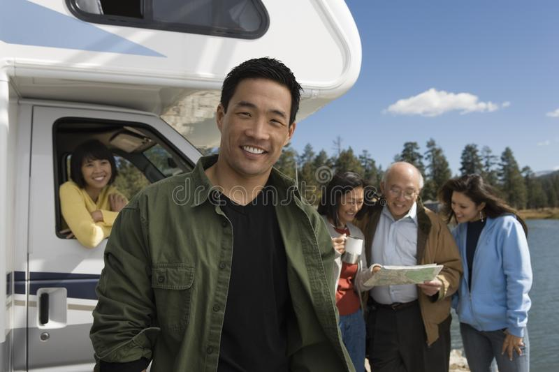 Man standing in front of RV at lake with family stock photo