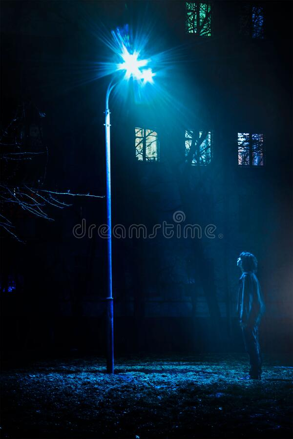 Man Standing in Front of Street Light Turned on stock image