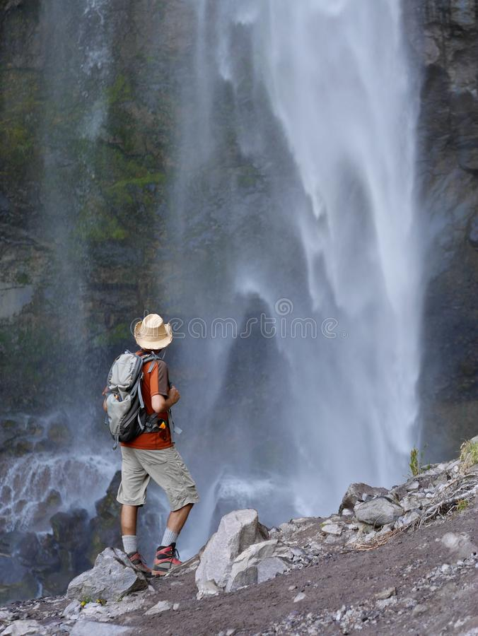 Man standing in front of waterfalls. royalty free stock photography