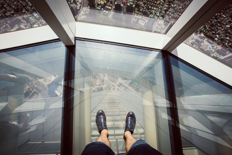 Man standing on a glass floor at Lotte Tower observation deck royalty free stock photography