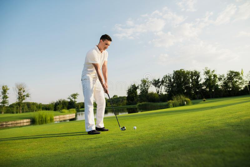 A man is standing on a golf course and getting ready to hit the ball with a golf club stock images