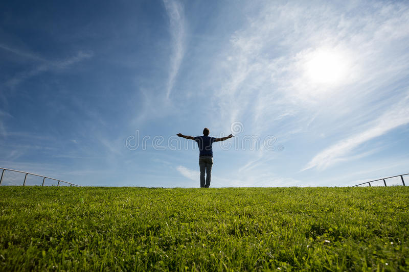 Man standing on grass in sunlight. Silhouetted man standing on grass in sunlight stock photo
