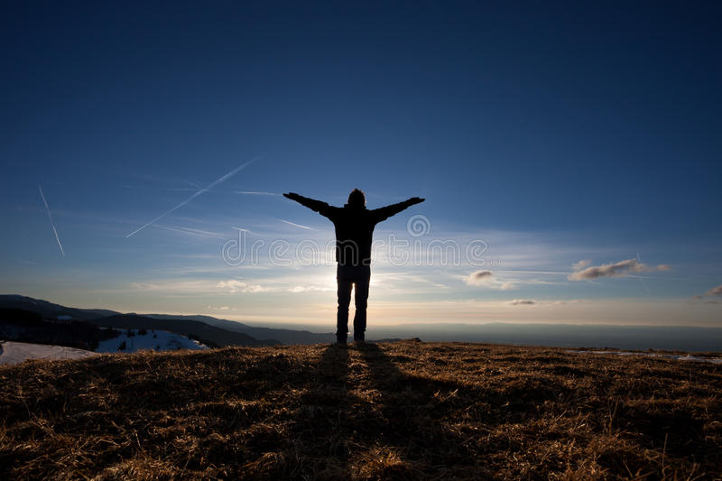 Man standing on grassy hill in sunset. Man standing in sky on grassy hill in sunset stock images