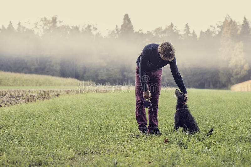 Man standing in green grassland bending down to pat his black do. Retro image of a man holding a leash standing in green grassland with forest and mist in royalty free stock photo