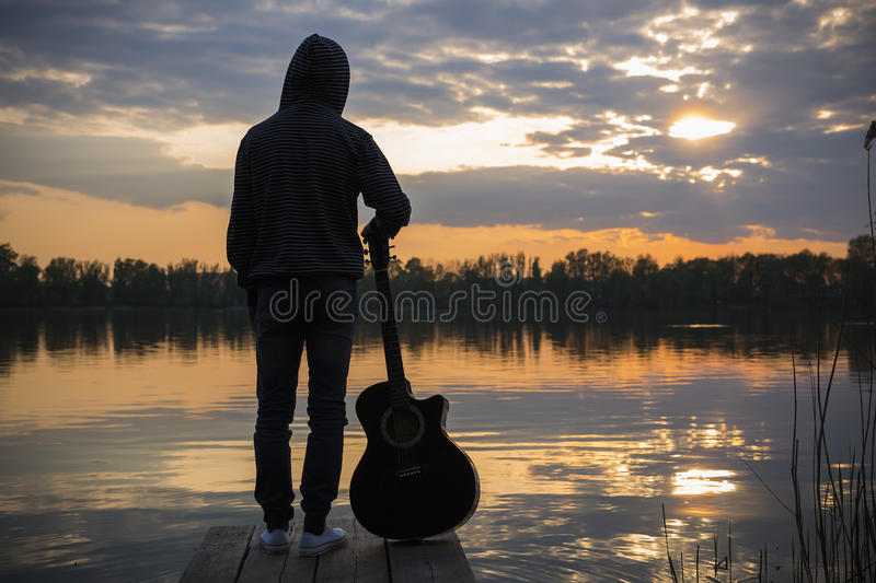 Man standing with guitar in sunset time stock photos