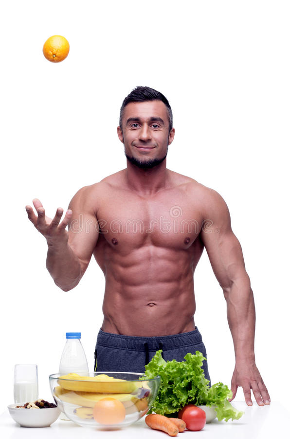 Man standing with healthy food. Cheerful muscular man standing with healthy food royalty free stock photos