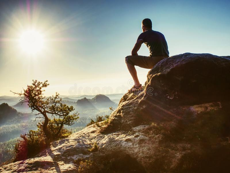 Hiker climbed up to rocky peak and enjoy view to valley bellow royalty free stock images
