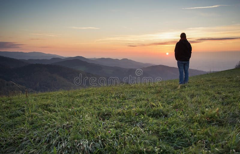 Man standing on hill in black forest at sunset. Man standing on hill in black forest, Germany at sunset stock photo