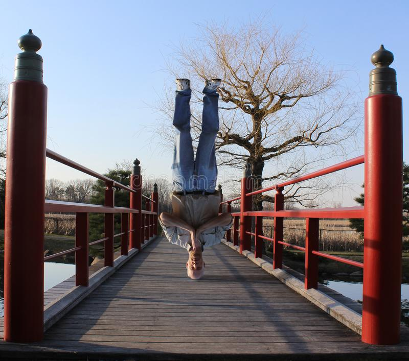 A Man Standing on his Head on a Japanese Bridge stock photography