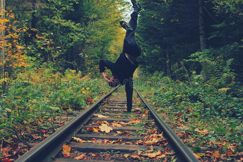 Man Standing With His Right Hand on the Train Rails in Middle of Forest stock photography