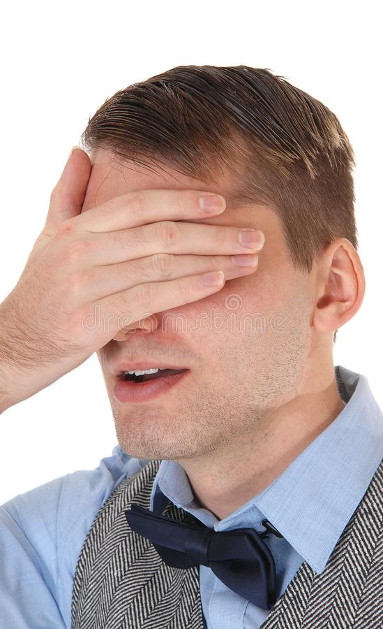 Man standing and holding hand over his eyes stock photo
