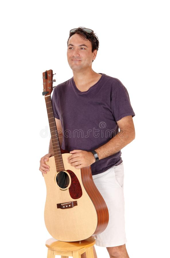 Man standing and holding his guitar, smiling stock photos