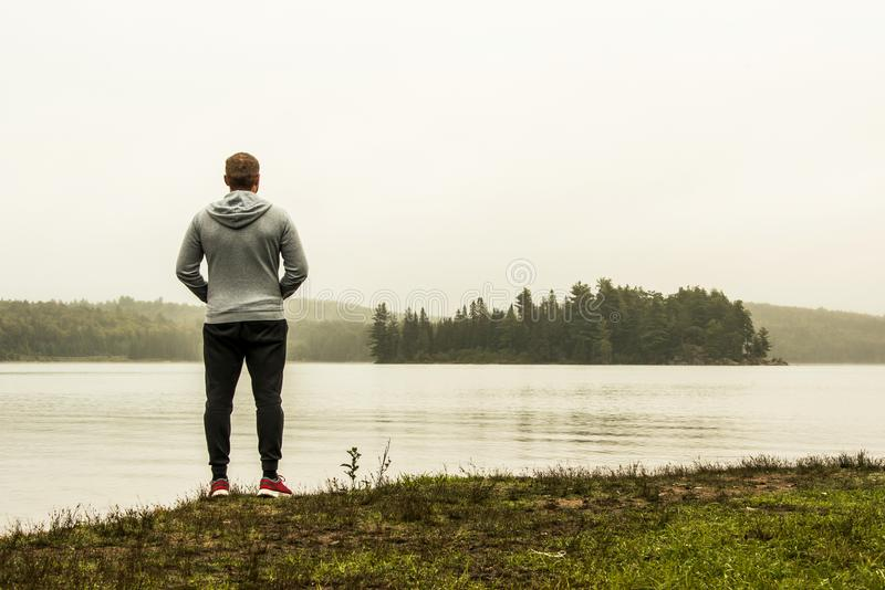 Man standing at lake of two rivers algonquin national park watching ducks Ontario Canada on a grey morning atmosphere stock photography
