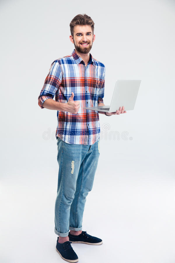 Man standing with laptop and showing thumb up sign. Full length portrait of a casual man standing with laptop and showing thumb up sign isolated on a white stock photos