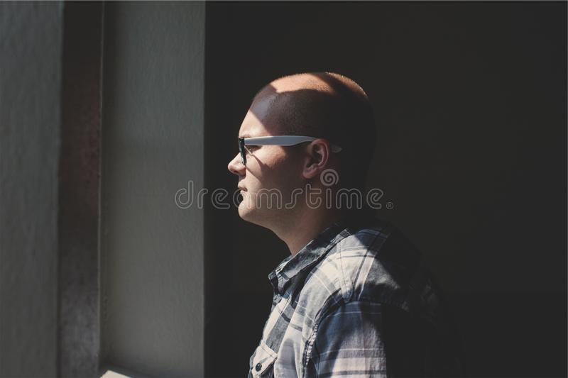 Man Standing Looking Straight Forward Through the Window stock photo