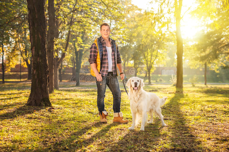 Man standing in a meadow and posing with a dog stock image