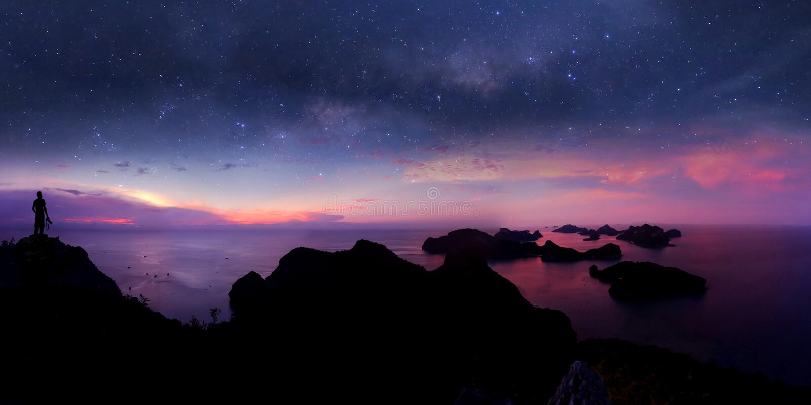 Man standing on the mountain with panorama view and million stars galaxy royalty free stock photos