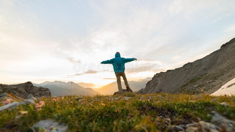 Man standing on mountain top outstretching arms, sunrise light colorful sky scenis landscape, conquering success leader concept. Man standing on mountain top royalty free stock images