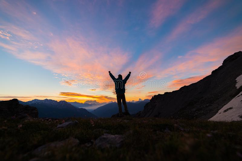 Man standing on mountain top outstretching arms, sunrise light colorful sky scenis landscape, conquering success leader concept. Man standing on mountain top stock image