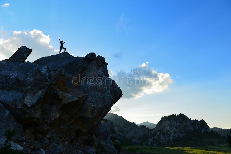 The Happiness of Your Adventurer in Discovery. Man standing on mountain top raising arms, sunrise light colorful sky scenis landscape, conquering success leader royalty free stock photos